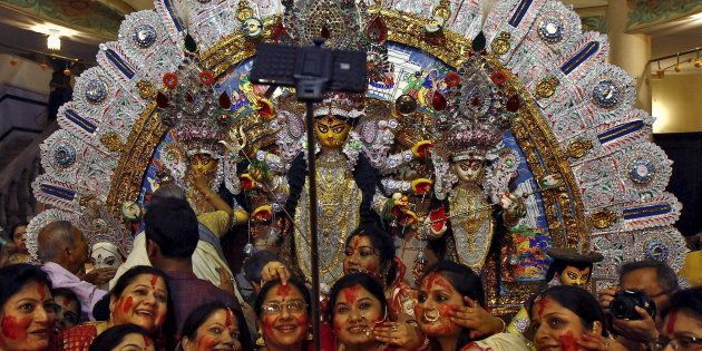 Hindu women use a selfie stick to take pictures after worshipping the idol of the Hindu goddess Durga...