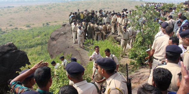 Indian police and bystanders gather at the site where eight SIMI activists, who escaped from Central...