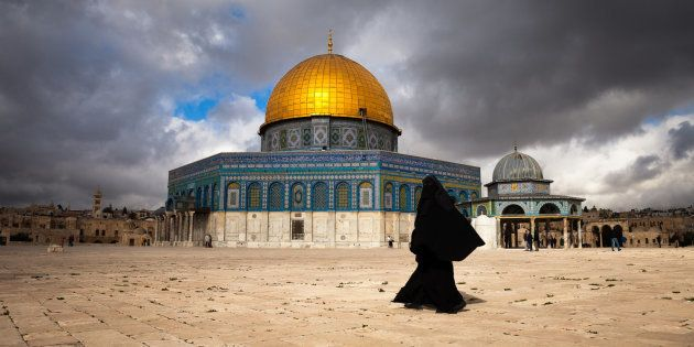 Muslim woman walking by the Dome of the Rock in