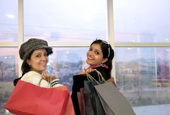 Group of happy smiling women shopping with colored