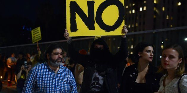 A protester holds a placard as a freeway was shutdown in downtown Los Angeles, California on November...