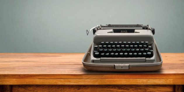 Old retro Typewriter on table with vintage gray gradient background
