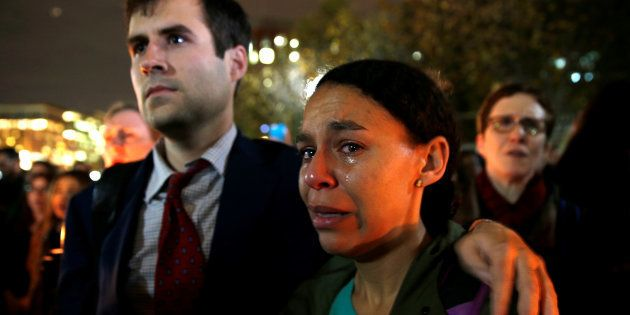 A woman cries while taking part in an anti-Trump candlelight vigil in front of the White House in Washington...