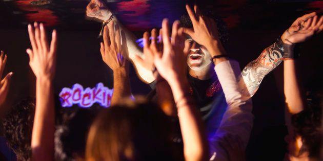 DJ playing with in nightclub, people dancing in