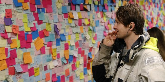 A man stops to read messages written on post-it notes regarding the election of President-elect Donald...