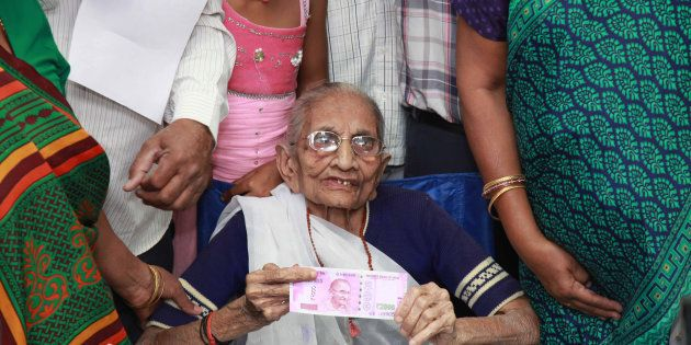 Indian Prime Minister Narendra Modi's mother (C) holds up a 2,000 rupee note after exchanging money at...
