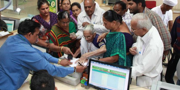 Indian Prime Minister, Narendra Modi's mother Heera Ba Modi (C) exchanges money at a bank in Rysan village,...