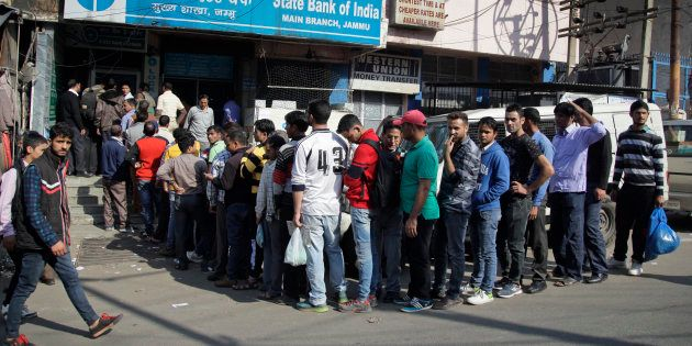 People wait in a queue to deposit or exchange discontinued currency notes outside a