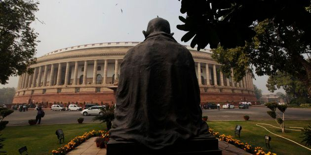A bird sits on a statue of Mahatma Gandhi outside the parliament building in New Delhi, India, Tuesday,...