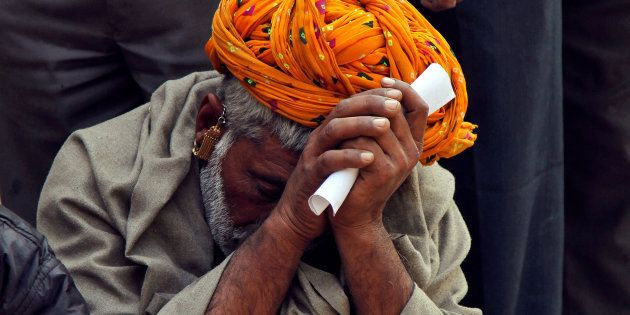 A man sits in a queue to deposit his old high denomination banknotes in Ajmer, India, November 16,