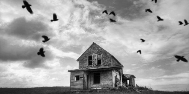An abandoned farmhouse with murder of crows.
