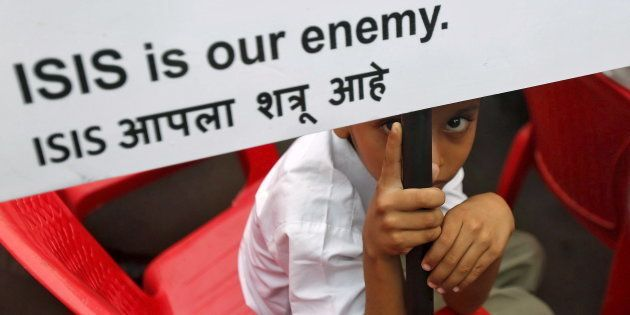 A Muslim boy looks on as he holds a placard at a rally organised by a Muslim charitable trust in Mumbai,...