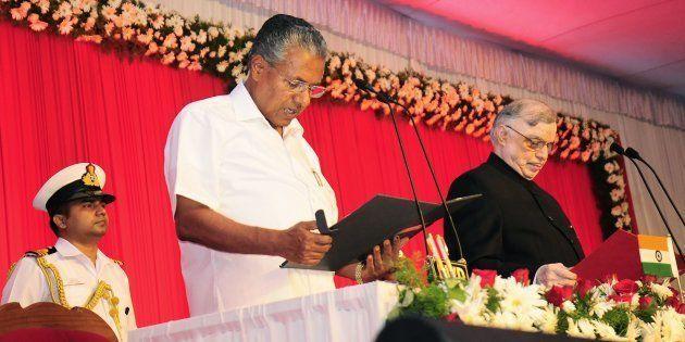 Incoming Chief Minister of Kerala Pinarayi Vijayan (C) stands alongside Governor of Kerala P. Sathasivam...