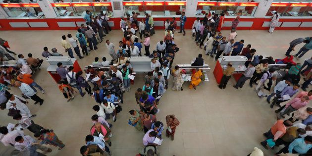 People wait in queues to deposit and withdraw money at a post office in Lucknow, India, November 10,...