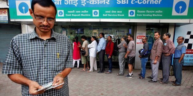 A man counts his money after withdrawing from an ATM even as people are seen waiting in long queues for...