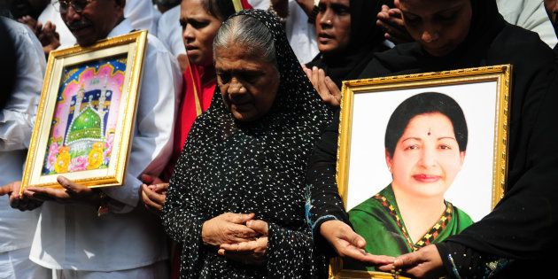Indian Muslims hold a portrait of Tamil Nadu Chief Minister Jayalalitha Jayaram as they pray for her...