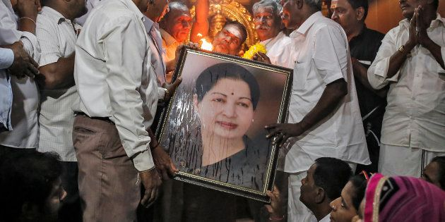 Well wishers of Tamil Nadu Chief Minister Jayalalithaa Jayaraman hold her portrait as they pray at a...