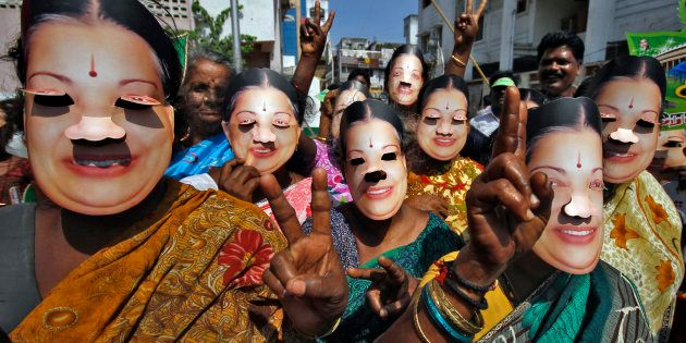 Supporters of J. Jayalalithaa wear masks as they gesture during an election campaign ahead of the general...