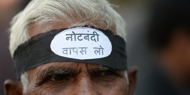 An activist from the Communist Party of India wearing a headband shouts slogans against the government...