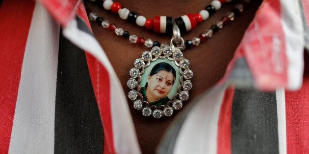 Jayalalithaa supporter wears a necklace with her picture as he attends a prayer ceremony at AIADMK office...