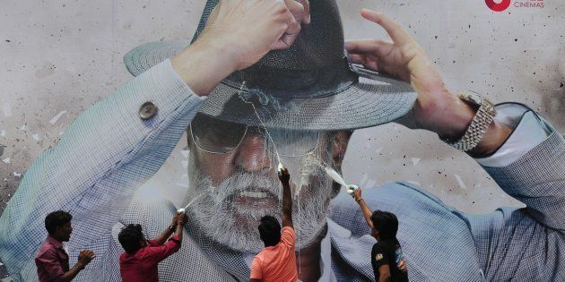 Indian fans spray milk on a poster of Bollywood star Rajinikanth outside a cinema on the first day of...