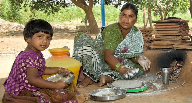 A mother prepares flat bread from pearl millet in Andhra