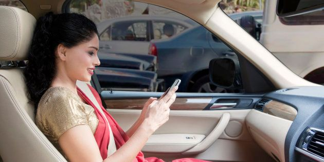 Indian young woman sending a text on mobile phone in car