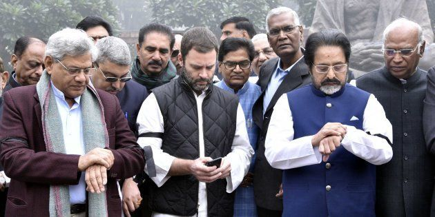 Opposition members check watches, look at their phone, while staging a protest near the Gandhi Statue...