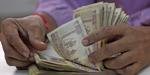 A man counts old 500 and 1000 notes inside the bank at Vashi, on November 21, 2016 in Mumbai,