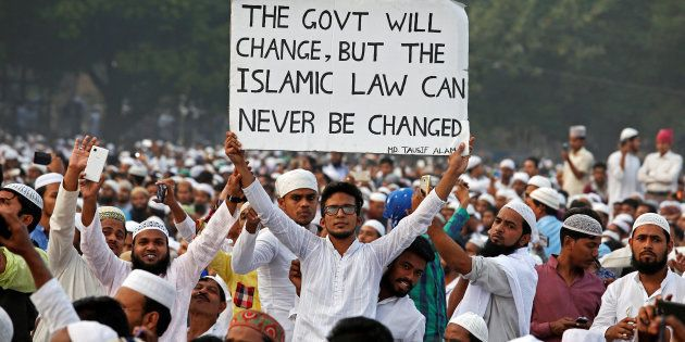 A man holds a banner during a rally organised by All India Muslim Personal Law Board (AIMPLB) in support...