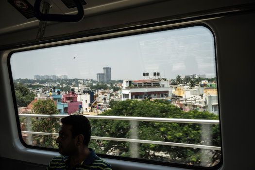 A passenger is silhouetted in front of a window as he rides a train, operated by Bangalore Metro Rail...