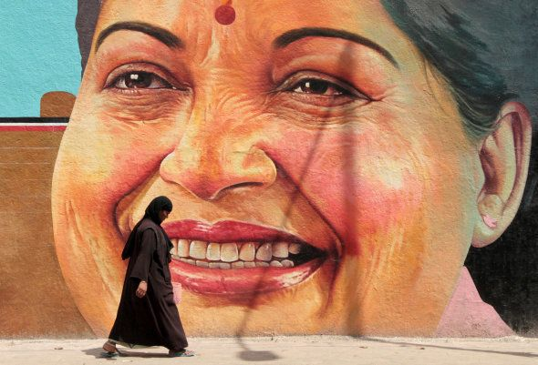 A woman walks past a portrait of J. Jayalalithaa, Chief Minister of the southern state of Tamil Nadu,...
