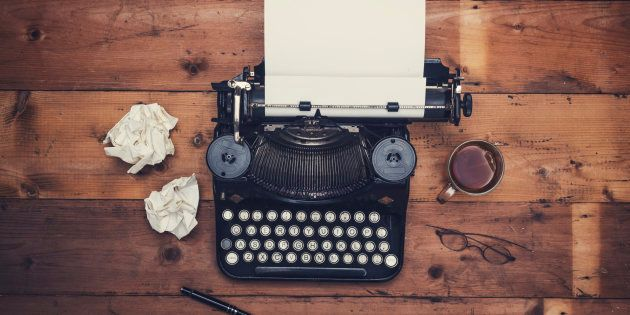 Top view thirties retro writers desk with typewriter on old wooden background table