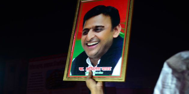 An Indian supporter of Uttar Pradesh's Chief Minister Akhilesh Yadav holds the photograph of Akhilesh...