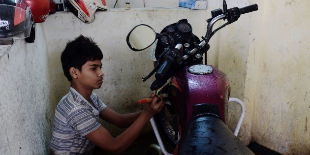 Bangladeshi worker Russel, and who says he will turn 14 next year, works in a garage in Dhaka on December...