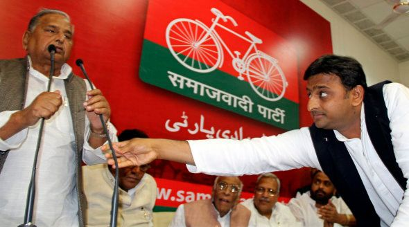 Akhilesh Yadav adjusts microphone for his father, the Samajwadi Party President Mulayam Singh Yadav,...