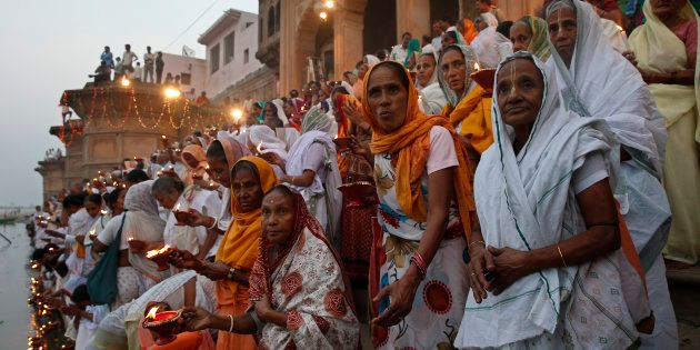 Widows, who have been abandoned by their families, hold earthen oil lamps as they offer prayers on the...