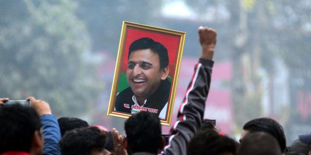 An Indian supporter of Uttar Pradesh's Chief Minister Akhilesh Yadav holds the photograph of Akhilesh...