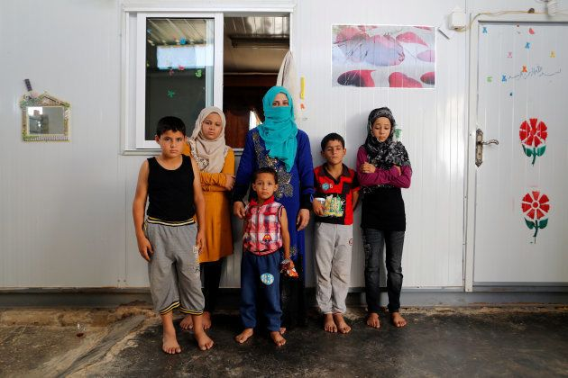 Rasha Inha, 30, the Syrian widow of a rebel fighter, poses for a photograph with her children in Zaatari...