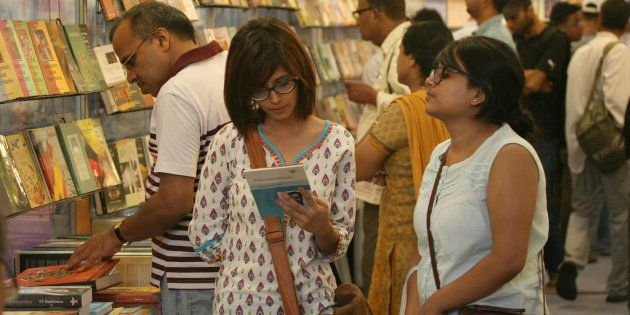 Visitors read books displayed at the 20th Delhi Book Fair organized by the Indian Trade Promotion Organisation...