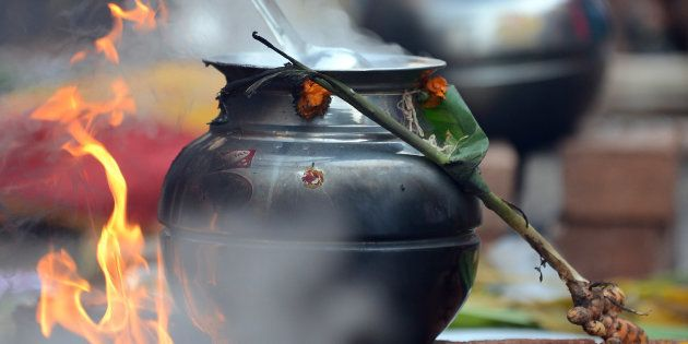 A Hindu devotee cooks a traditional sweet dish during the Pongal festival in Mumbai on January 14, 2013....