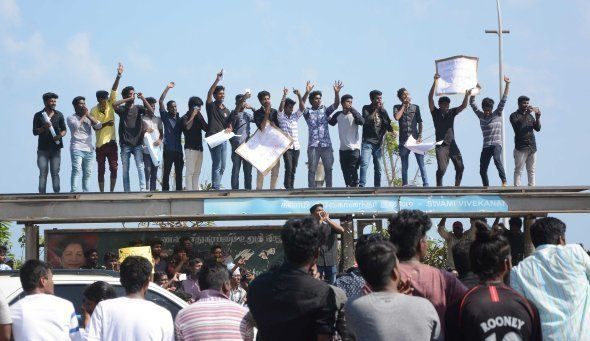 Indian students shout slogans from the top of a bus during a demonstration against the ban on the Jallikattu...