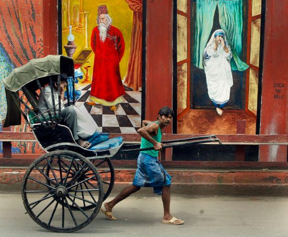 An Indian rickshaw-puller passes murals depicting India's famous Nobel laurete poet Rabindranath Tagore...