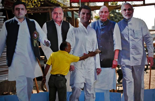 A worker cleans a cut-out of Rahul Gandhi (C) India's ruling Congress party Vice President, beside cut-outs...