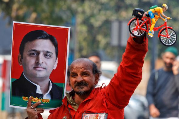 A Samajwadi (SP) party worker holds a toy bicycle representing the party's symbol and a poster of chief...