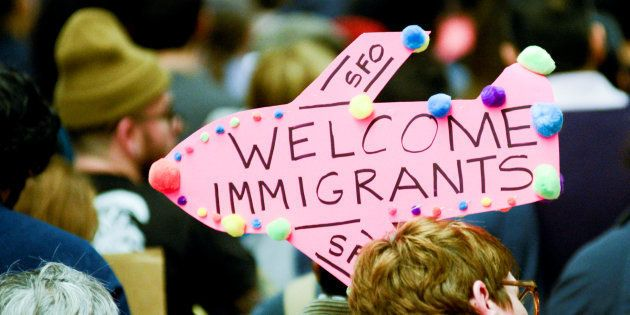 Demonstrators hold welcome signs for immigrants during second day of anti-Donald Trump immigration ban...