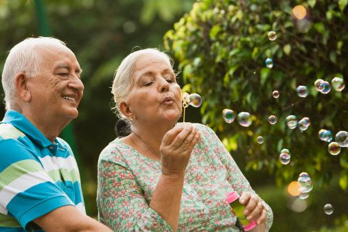Senior couple blowing bubbles with wand