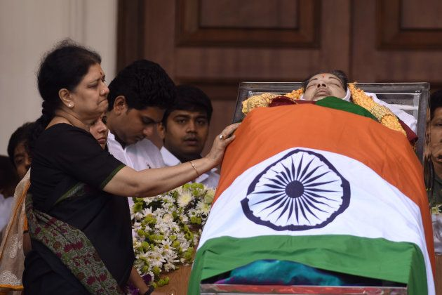 In this photograph taken on December 6, 2016, close aide, VK Sasikala (L) stands next to the mortal remains...