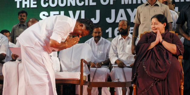 O. Paneerselvam bows to J. Jayalalithaa (R) before taking his oath as state's finance minister during...