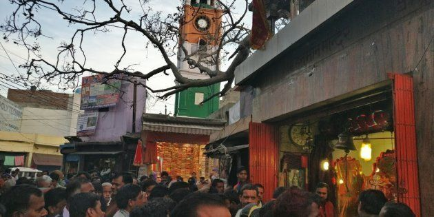 People crowd around a temple in Kasganj, overlooking the clock tower, as it is visited by the BJP's candidate,...